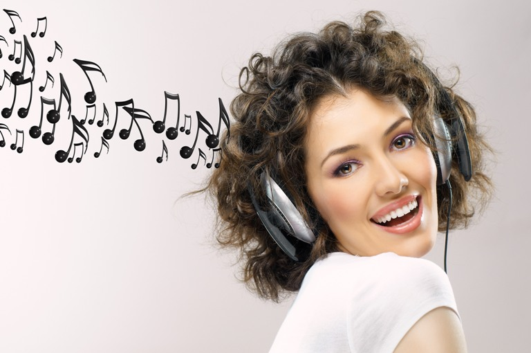 girl with headphones on the grey background